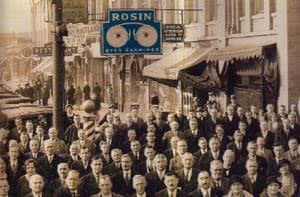 A sepia-toned image of Rosin Eyecare's earlier location. The Rosin sign has been artificially colored blue at a later point.